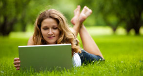 Woman using laptop in green field